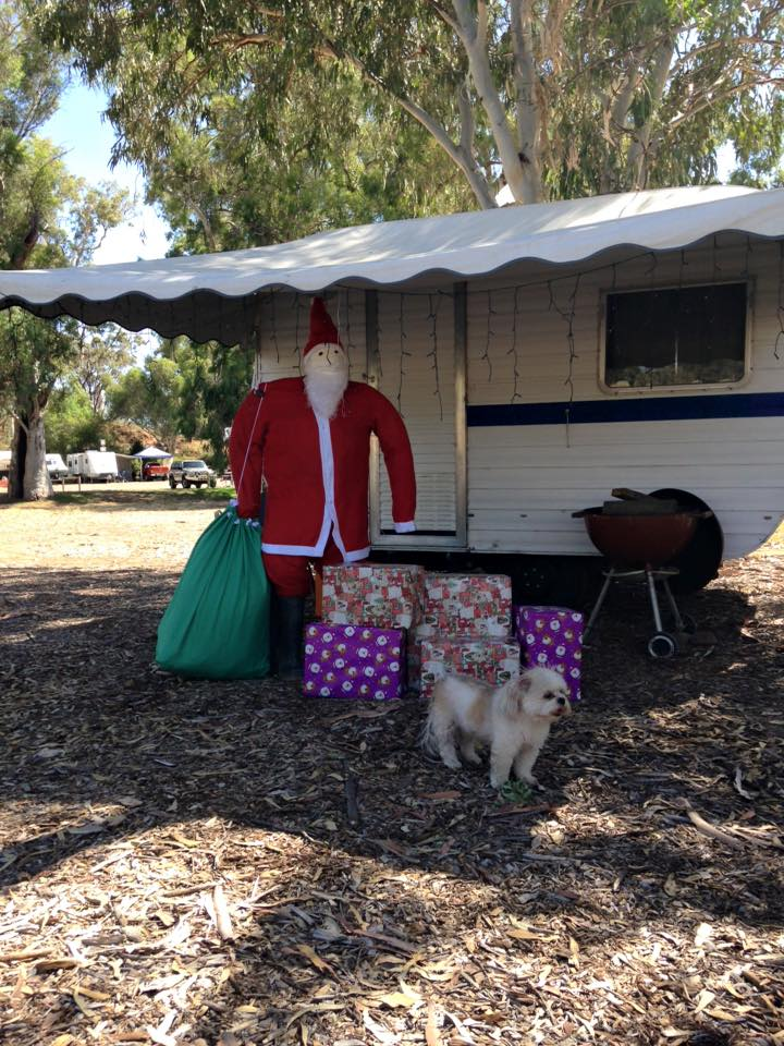 Santa with presents in front of caravan