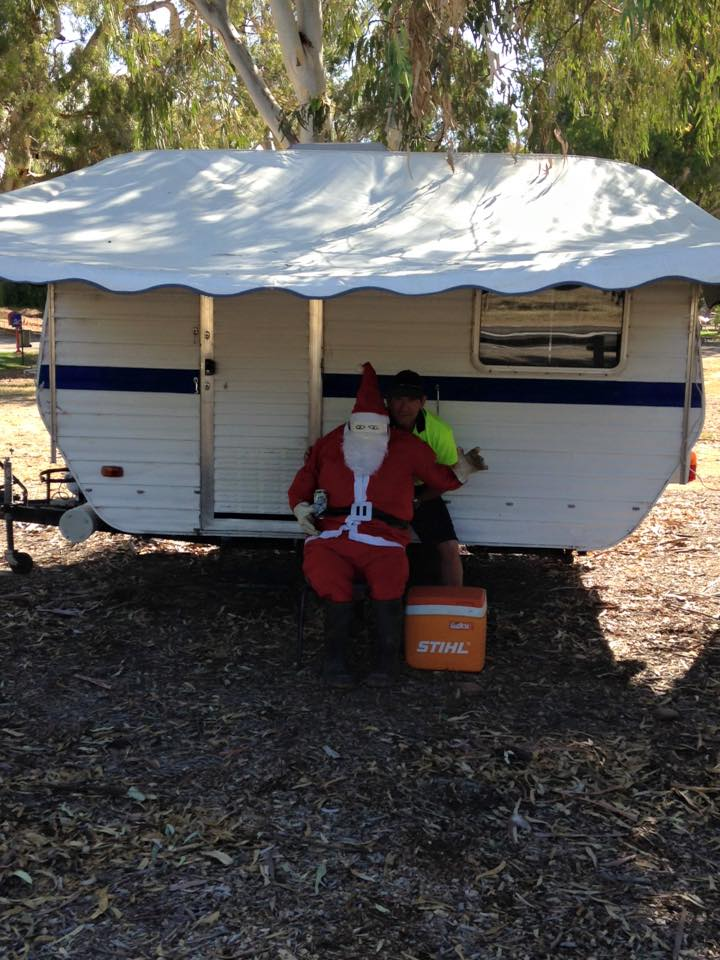 Santa sitting in front of a caravan